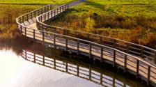 Rounded wooden pedestrian bridge across river