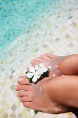Woman feet in water at swimmingpool
