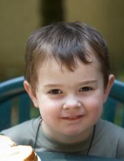 Cute 3 year old boy grinning