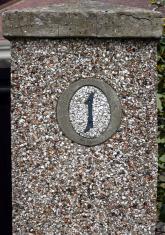 No 1 Sign on pebbledashed pillar
