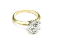 gold engagement ring lying on white