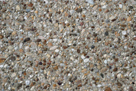 Multicoloured pebbles and various stones in grey sand