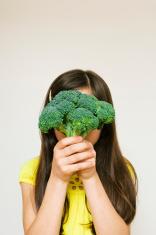 Young Girl Hiding Behind Broccoli