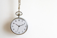 Silver pocket watch hanging in chain against white background