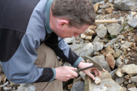 male geologist scientist with hammer studying rock sample