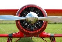 Vintage red biplane radial engine, spinner and propeller