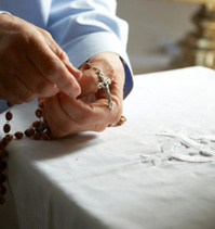 Woman hands with crucifix rosary beads
