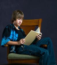 Teenage boy reading while seated