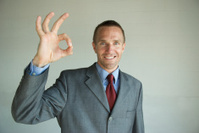 Smiling Businessman Makes OK Sign