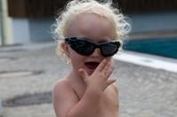Cooles Baby mit Brille lacht hinter vorgehaltener Hand