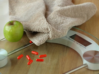 Diet pills on a bathroom scale