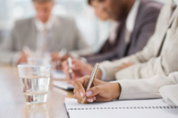 Closeup of businesspeople writing