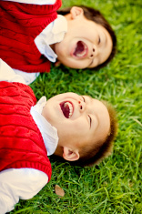 joyous moment between brothers laying on grass