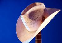 Western Hat On Guitar Neck Blue Background