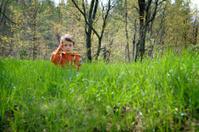 boy sitting in grassy field