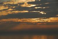 Lonely sailboat under sunset cloudscape