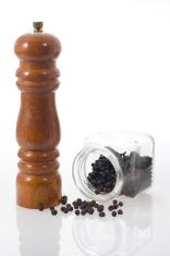 Pepper grinder and black peppercorns.