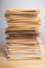 Pile of Paperwork on Wood Desk