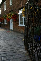 iron gates leading to flower baskets