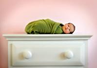 Swaddled baby on a dresser
