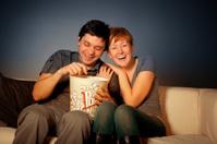 Happy couple watches TV