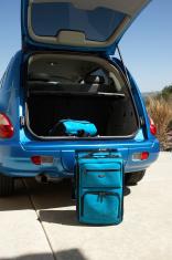 Suitcases by open door of car