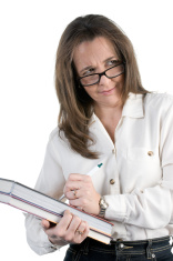 Middle-aged school teacher looks over her eyeglasses while takin