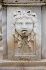 Female face on old roman fountain