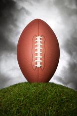 American football against grey cloudy sky