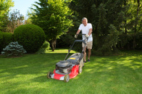 Middle aged man is working with the lawn mover.