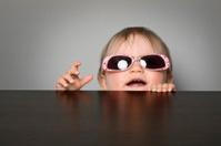 Baby girl peeking over a table