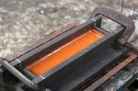 Molten glass in graphite mould