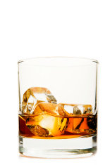 glass with whisky and ice cubes on white