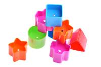 Various coloured blocks for shape sorter toy isolated on white