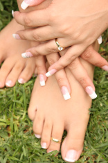 Engagement ring on hands holding feet