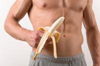 Shirtless muscular Man holding a peeled Banana