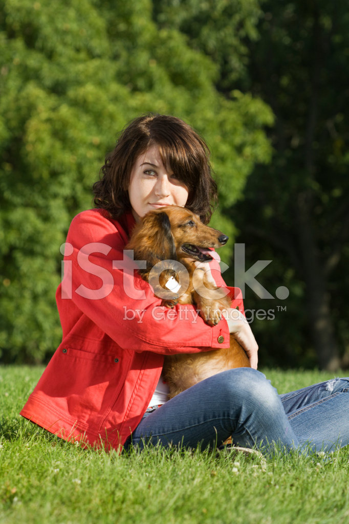 Smiling Mature Mexican Woman With Her Dachshund Dog Standing On Stone Stairs In Forest Stock Photo