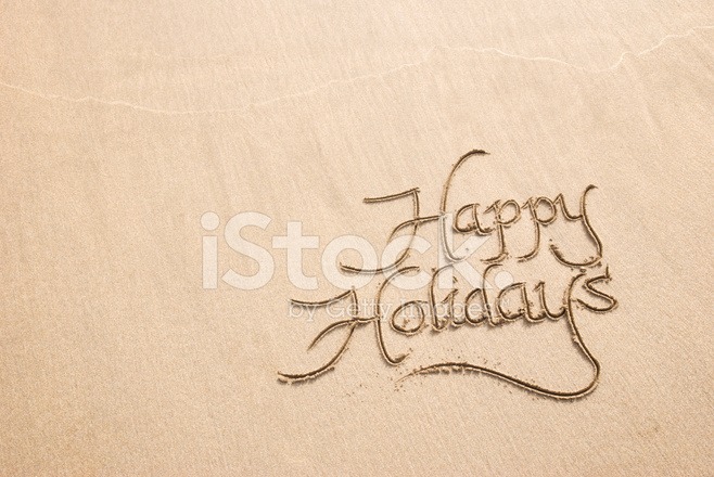 Happy holidays calligraphy greeting message in sand stock photos
