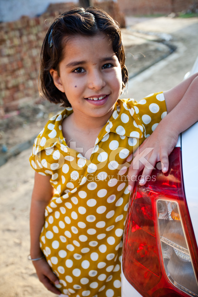 cheerful little indian girl standing besides the car natural lig