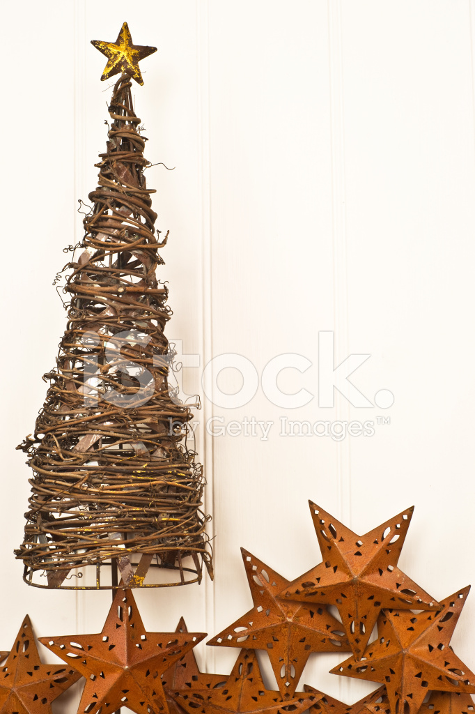 metal christmas tree with rusty star decorations against panelle
