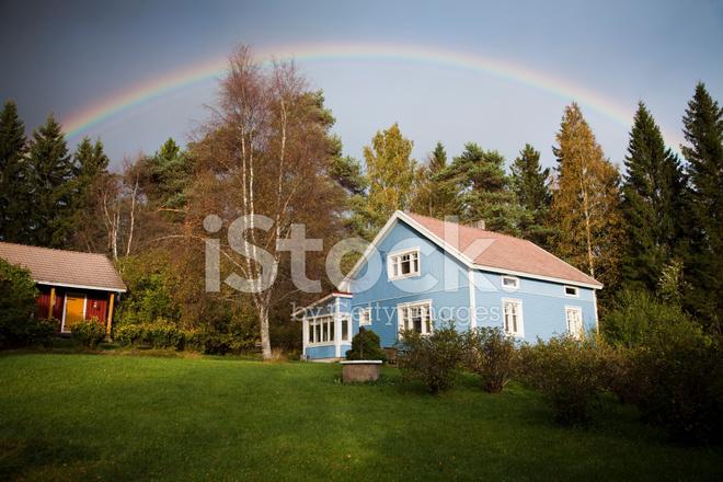 premium stock photo of blue house under rainbow