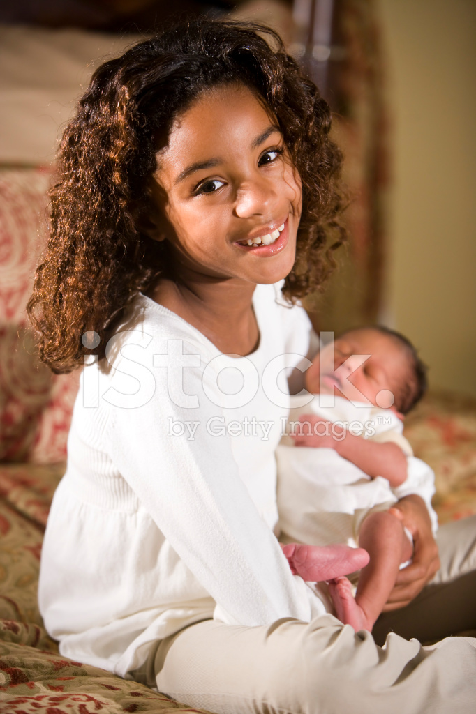African American Child Holding Tiny Newborn Baby Stock