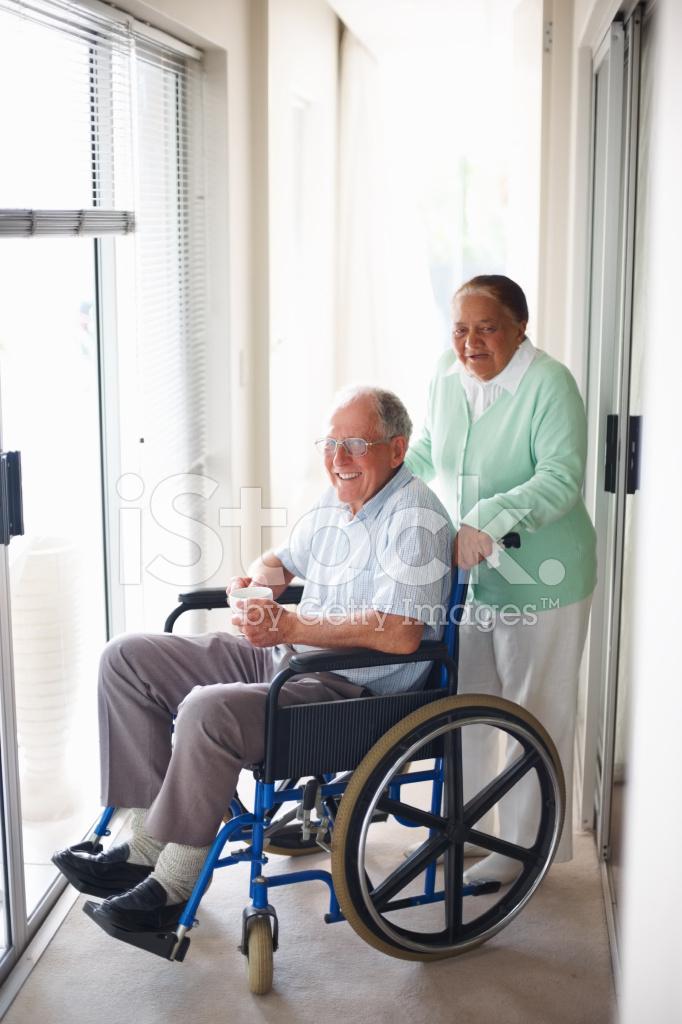 Femme g e aider son mari assis sur une chaise roulante for Assis sur une chaise