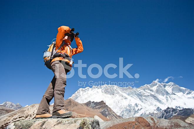 Weibliche wanderer blick durchs fernglas lhotse im stockfotos