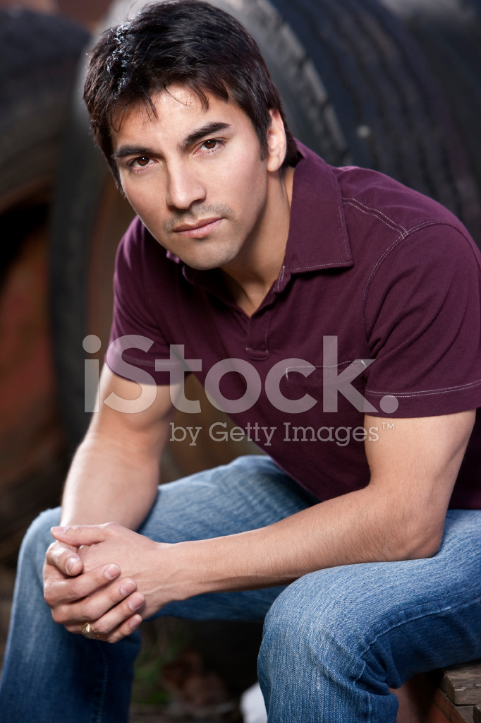3 4 view of handsome hispanic young man sitting copy space stock