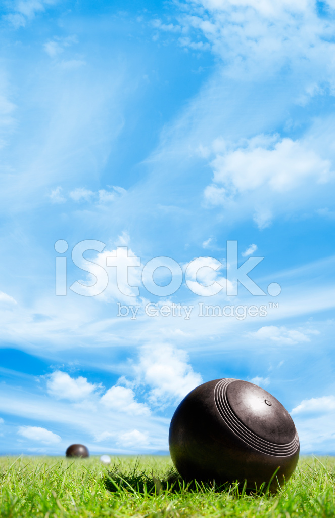 Wooden Lawn Bowls On Green Grass With Blue Sky Stock