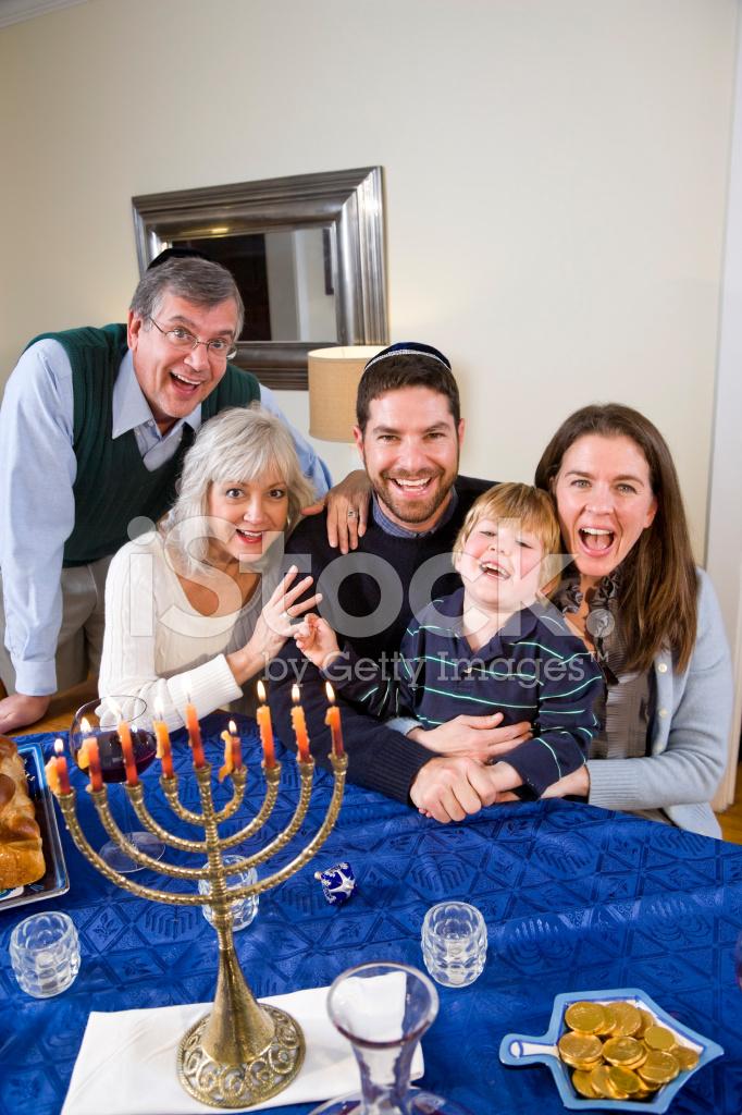 jewish family celebrating chanukah stock photos