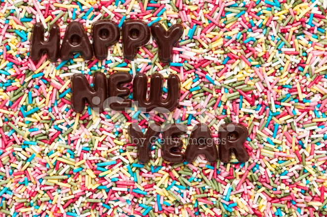 happy new year made of chocolate letters on colorful sprinkles