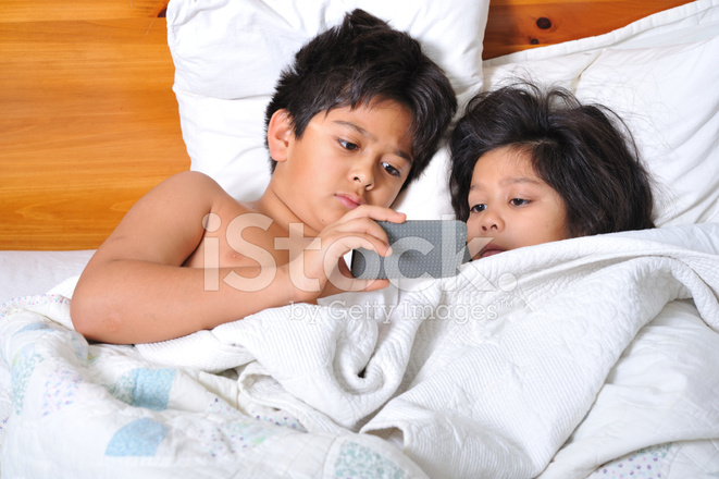 Boy And Girl In Bed Watching Movie On Portable Player Stock Photos