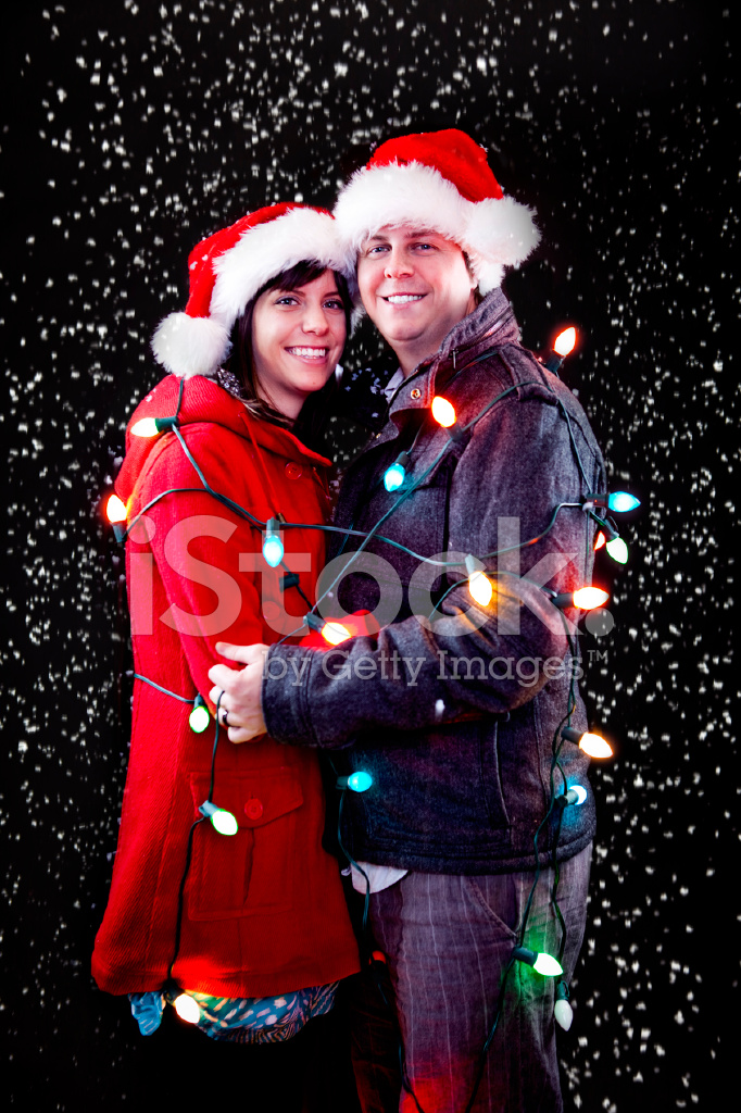 holiday couple wrapped in christmas lights